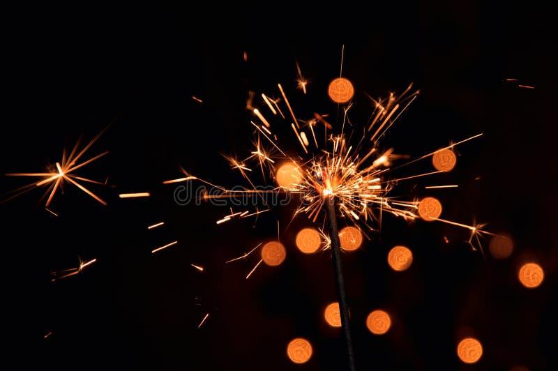 宏指令,关闭 与飞行火花的明亮的灼烧的闪烁发光物 与圣诞节诗歌选被弄脏的光的黑暗的背景  免版税库存图片