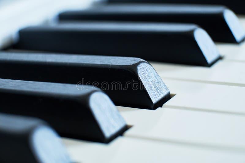 宏观特写镜头射击了白色的钢琴和黑钥匙浅景深 免版税库存照片