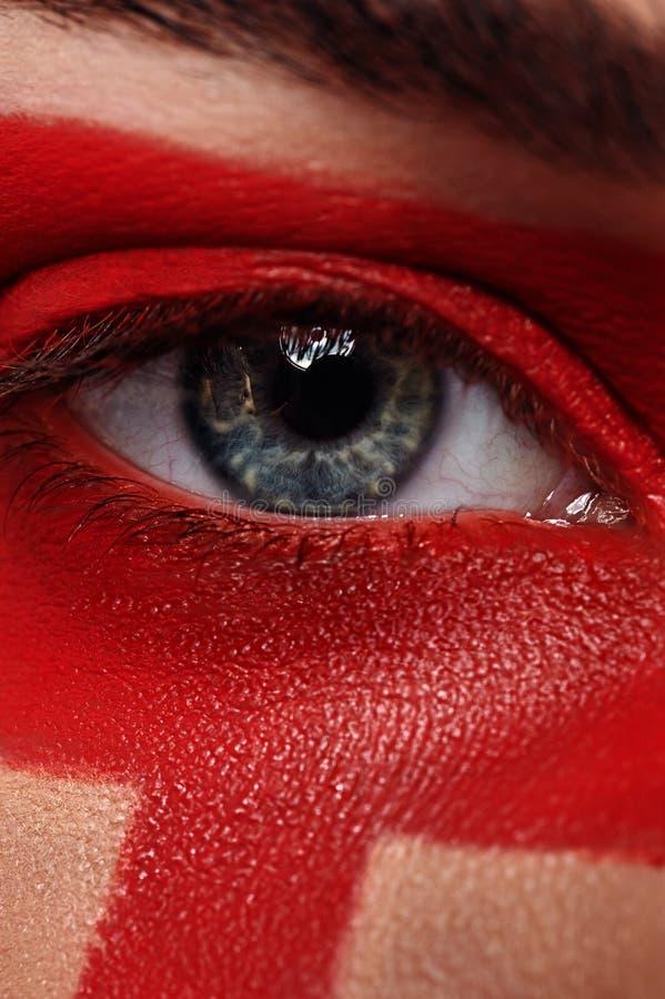 宏观秀丽开放眼睛和红色在皮肤化妆 免版税库存照片