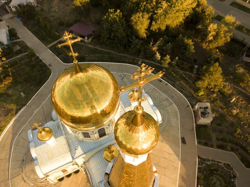 宗教十字架的空中关闭在使在日落f期间的金黄教会建筑学惊奇顶部 免版税库存照片