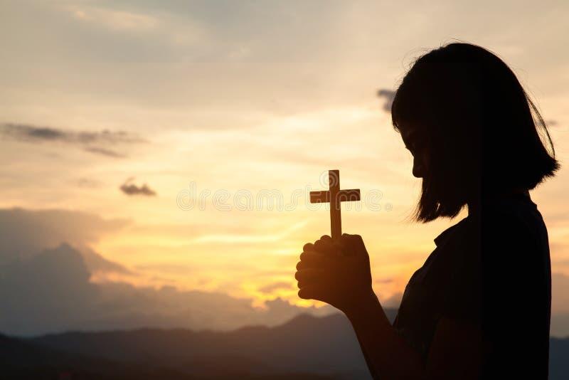 宗教概念 拿着耶稣受难象的女孩的剪影对上帝 与美好的日出,信念的标志的早晨 基督徒 免版税图库摄影