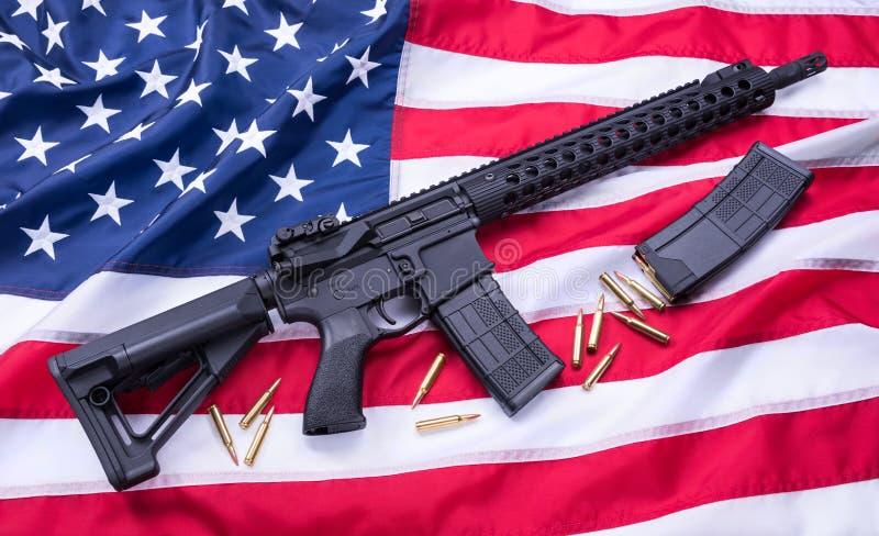 定制的AR-15马枪、子弹和一本杂志美国国旗表面,背景上 美丽的夫妇跳舞射击工作室妇女年轻人 库存图片