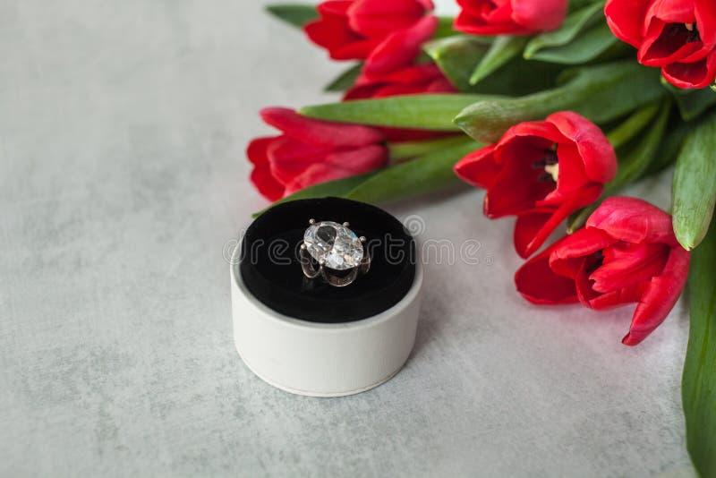 定婚戒指与在圆的白色箱子的巨型金刚石在提高灰色背景和与红色郁金香花束  库存照片