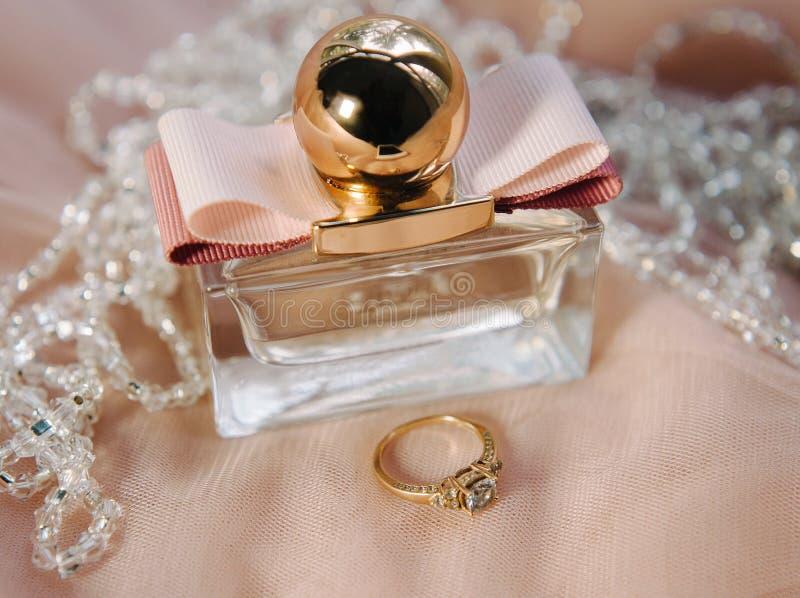 定婚戒指和香水、金子、白色和桃红色,婚姻的细节,新娘早晨 免版税库存图片