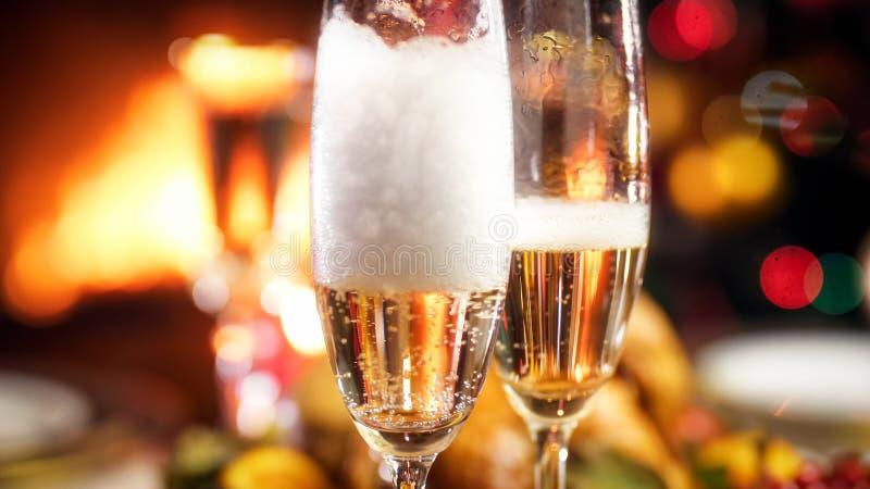 定居在两块玻璃中的香宾泡沫的特写镜头图象在Christamas晚餐 免版税库存图片