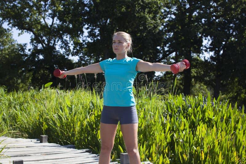 定调子运动白肤金发的与哑铃的女孩和举重,夏天 免版税库存图片