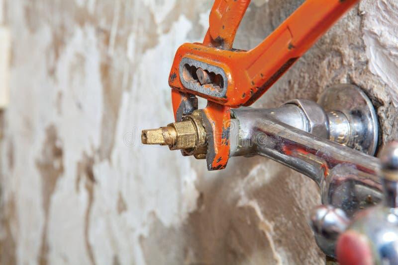 定象阀门轻拍用使用红色水管工钳子的漏的水 库存图片
