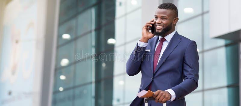 定购出租汽车 非洲商人到达对机场和谈话在电话 免版税库存照片