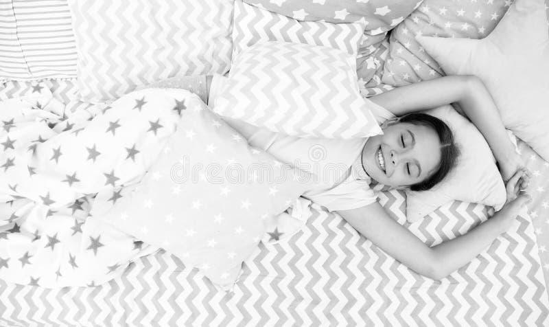 宜人唤醒 女孩微笑的愉快的孩子在与特征模式枕头和逗人喜爱的格子花呢披肩的床放置在她的卧室 免版税库存图片