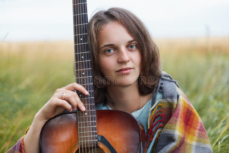 宜人女性特写有蓝色迷人的坐与吉他的眼睛和黑暗的短发的在看directl的绿色领域 免版税库存图片