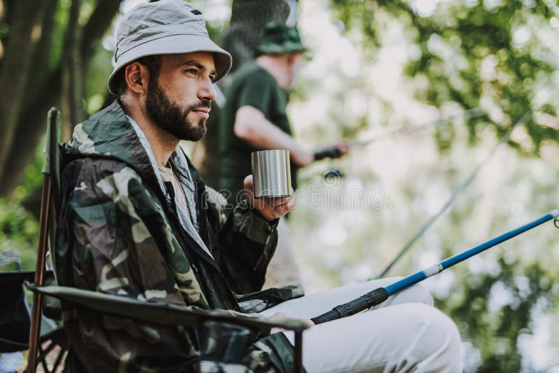 宜人的人饮用的刷新的饮料,当钓鱼时 免版税库存照片