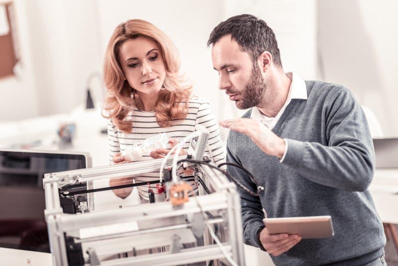 宜人的创造在3D打印机的男人和妇女原型 免版税库存图片