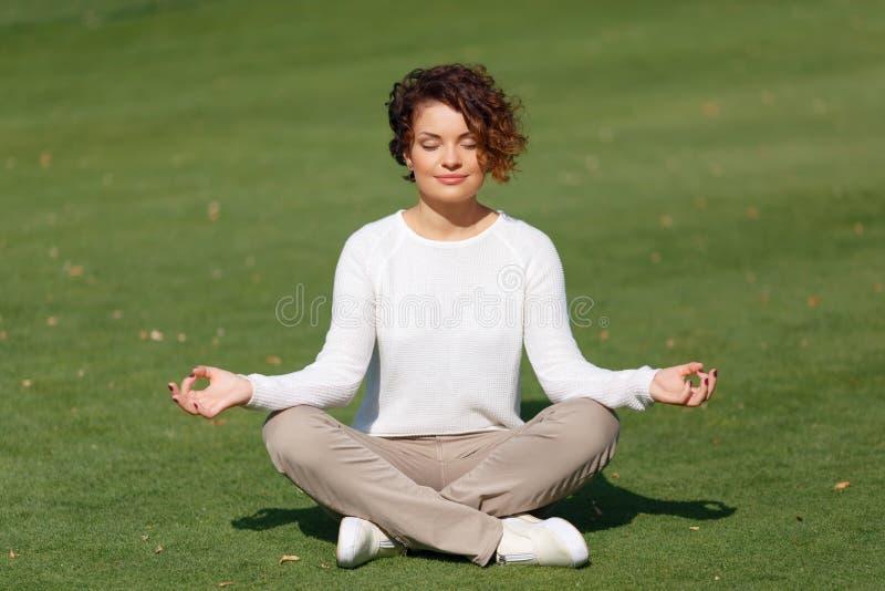 宜人的女孩实践的瑜伽 免版税库存照片