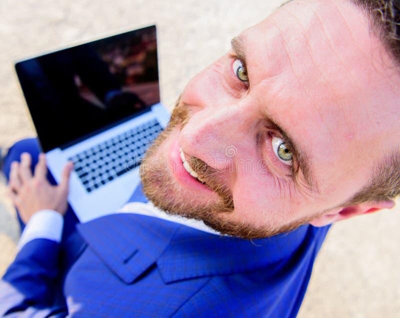 宜人的工作日户外 人微笑的快乐的面孔与膝上型计算机关闭一起使用 晴朗的夏日重要机遇 免版税库存图片