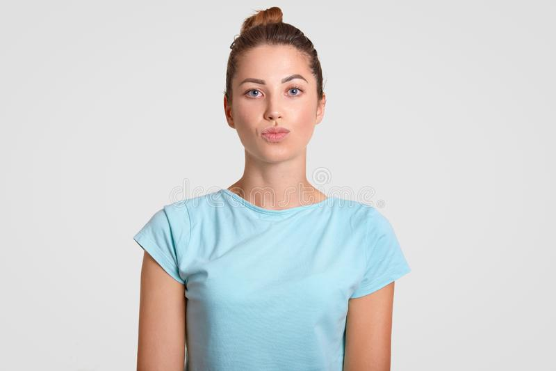 宜人的看的妇女水平的射击有健康皮肤的,在偶然蓝色轻的T恤杉保留嘴唇被环绕,穿戴,被隔绝的ov 库存照片