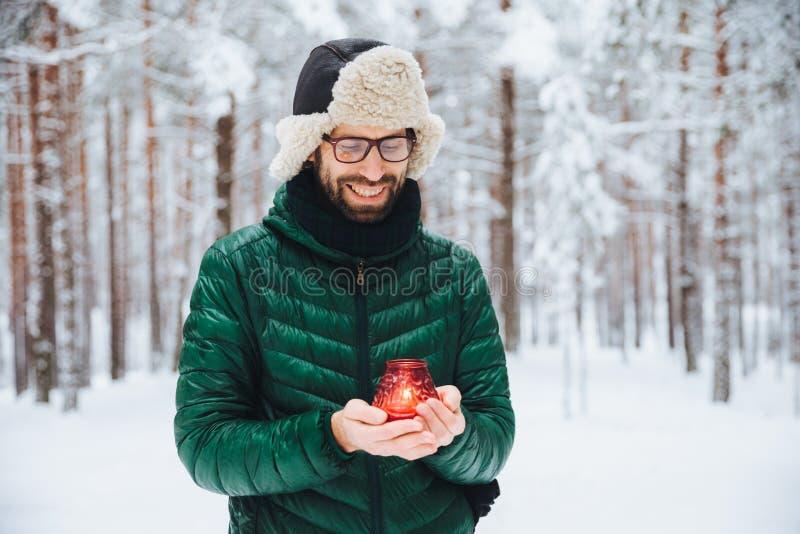 宜人的看的男性室外射击在手上举蜡烛,温暖手,愉快地看对此,立场在冬天森林包括w 库存图片
