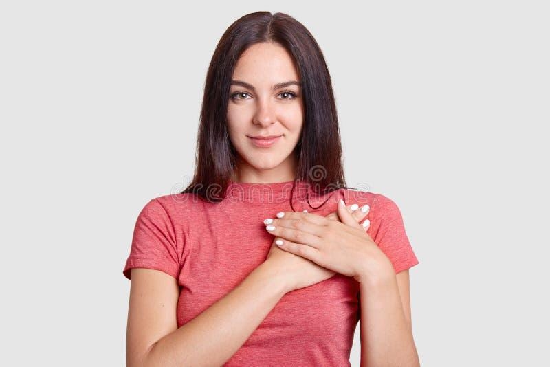 宜人的看起来的亲切的有之心的少妇演播室射击保留在胸口的手,用偶然T恤杉表示谢意,穿戴, pos 免版税图库摄影