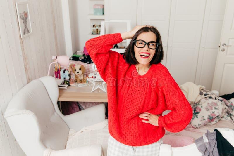 宜人的看起来的女性微笑室内射击快乐,佩带sp 免版税图库摄影