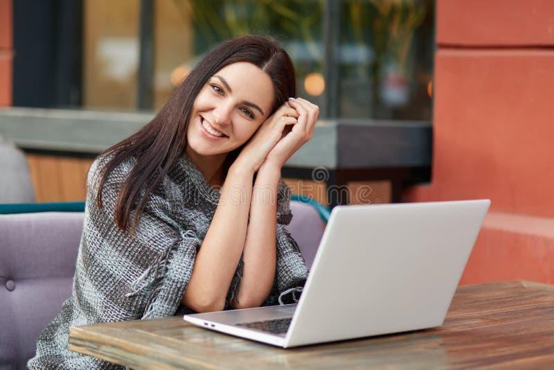 宜人的看起来的无忧无虑的年轻深色的女性照片在室外自助食堂享用备用的尖叉,遥远地研究便携式计算机 库存图片