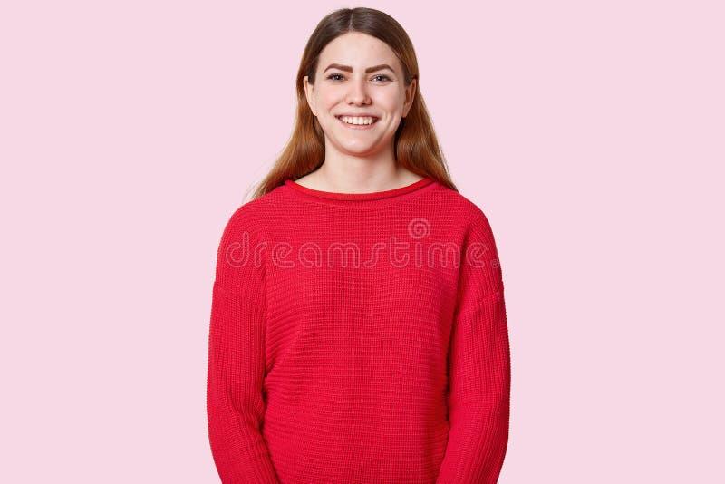 宜人的看起来的深色头发的年轻女人室内射击有暴牙的微笑的,在红色套头衫喜欢看宜人的事,穿戴 库存图片