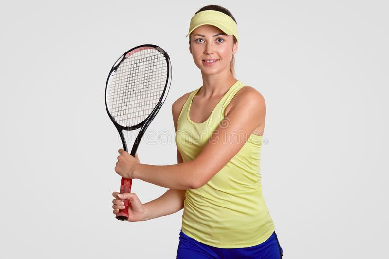 宜人的看起来的运动的坚定的女性演播室射击穿着法院盖帽、T恤杉和短裤,举行网球拍,是活跃p 库存照片