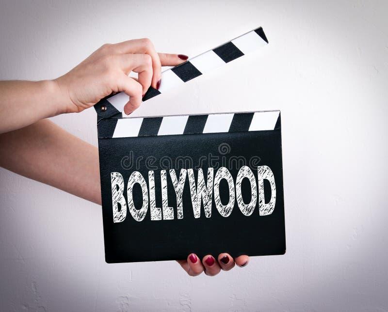 宝莱坞 拿着电影拍板的女性手 库存图片