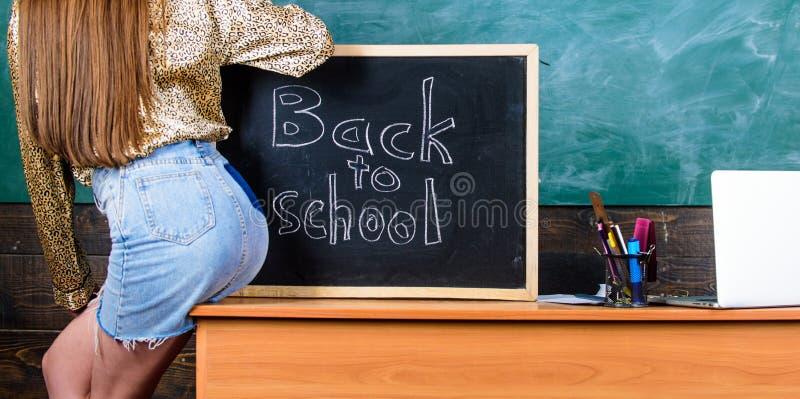 实习教师微型裙子性感的屁股坐桌黑板题字回到学校 女孩牛仔布裙子打破 库存照片
