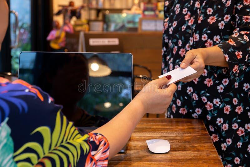 实施名片的女实业家对咖啡馆的顾客 库存图片