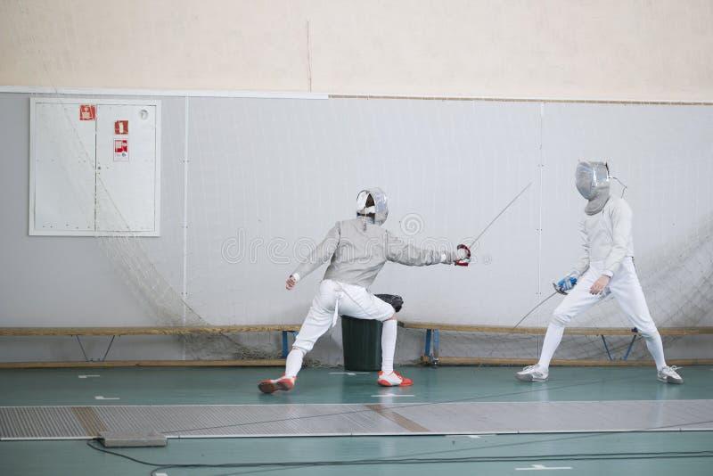 实践他们的与剑的两个少年击剑者战斗 库存照片