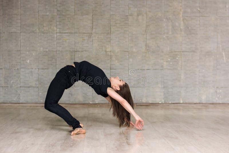 实践体操元素的女性舞蹈家 免版税库存照片