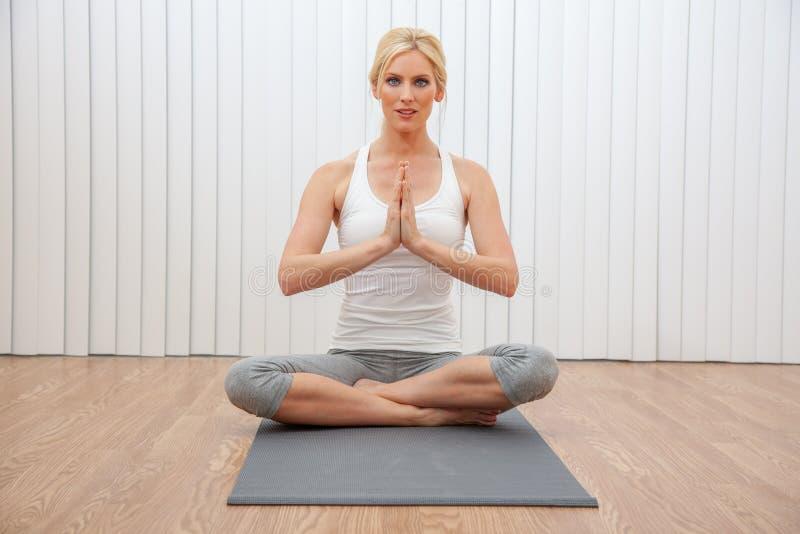 实践供以座位的瑜伽位置的年轻女性妇女 免版税库存照片
