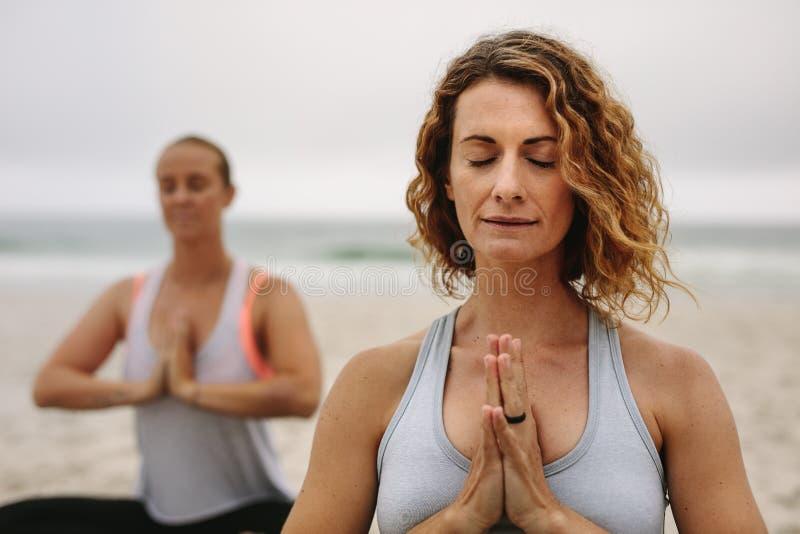 实践凝思和瑜伽的妇女在海滩 免版税图库摄影