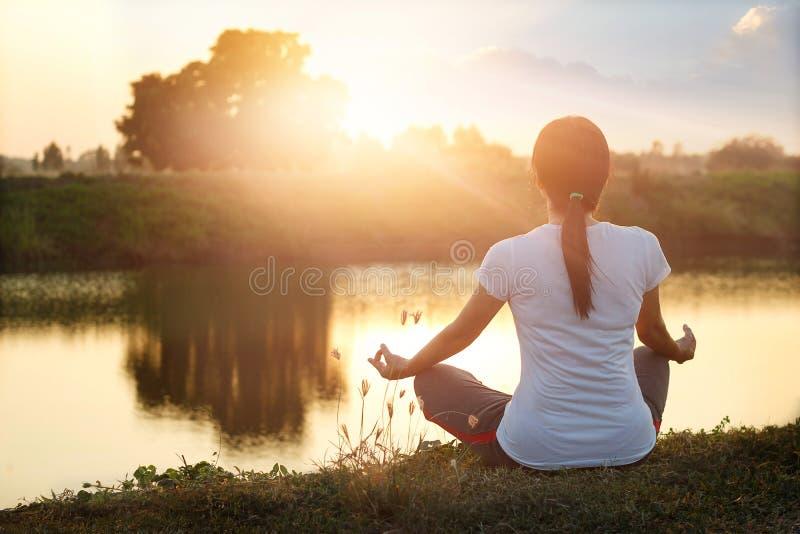 实践和思考由湖的少妇瑜伽在夏天 库存照片