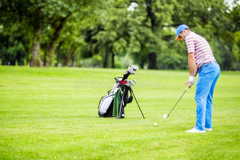 实践和集中在射击前后的高尔夫球运动员 库存图片