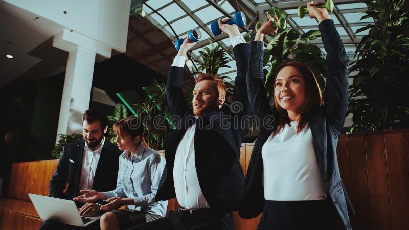 实践在一条长凳的男人和妇女在办公室 库存照片