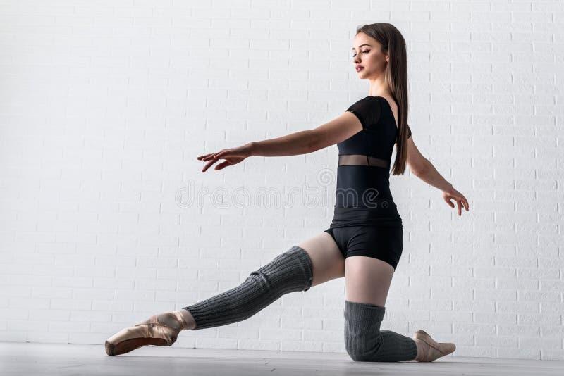 实践在她的艺术演播室地板上的芭蕾舞女演员  库存图片