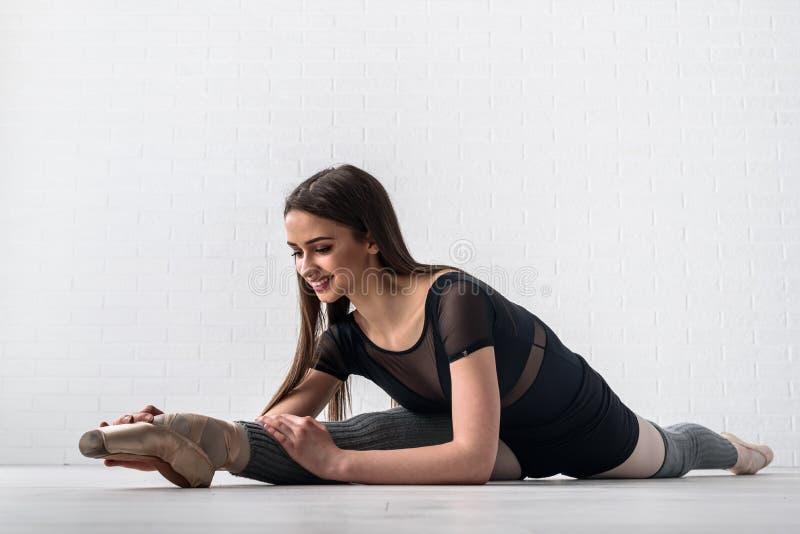 实践在她的艺术演播室地板上的芭蕾舞女演员  图库摄影