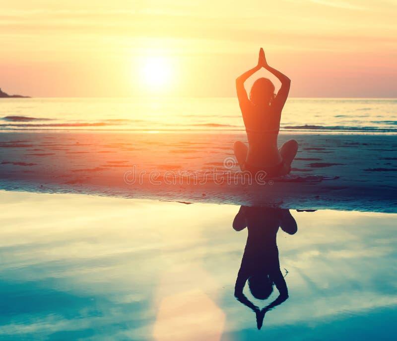 实践在日落的凝思、平静和瑜伽 自然 库存照片
