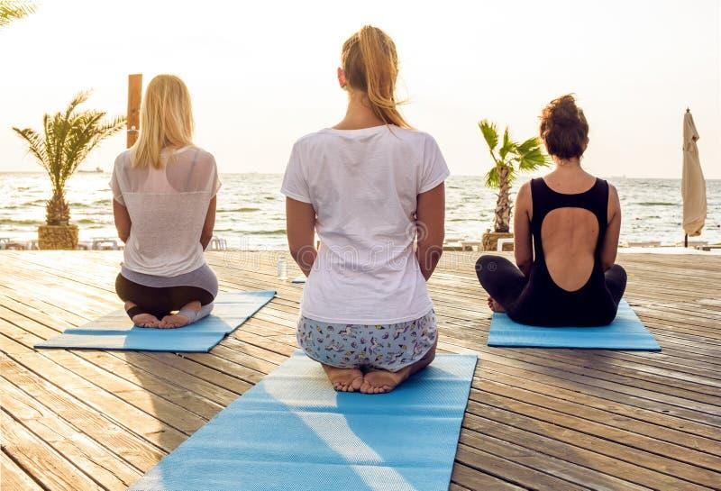 实践在海边的小组年轻女性瑜伽在日出期间 免版税库存照片