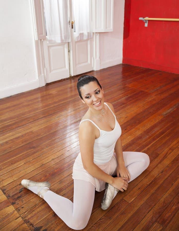 实践在硬木地板上的有吸引力的跳芭蕾舞者 库存照片