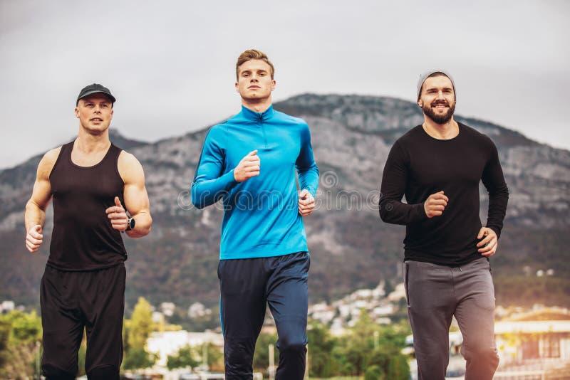 实践在竞技体育场轨道的运动员奔跑 免版税库存照片