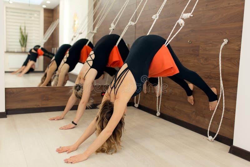 实践在绳索的妇女瑜伽舒展在健身房 r 免版税库存图片