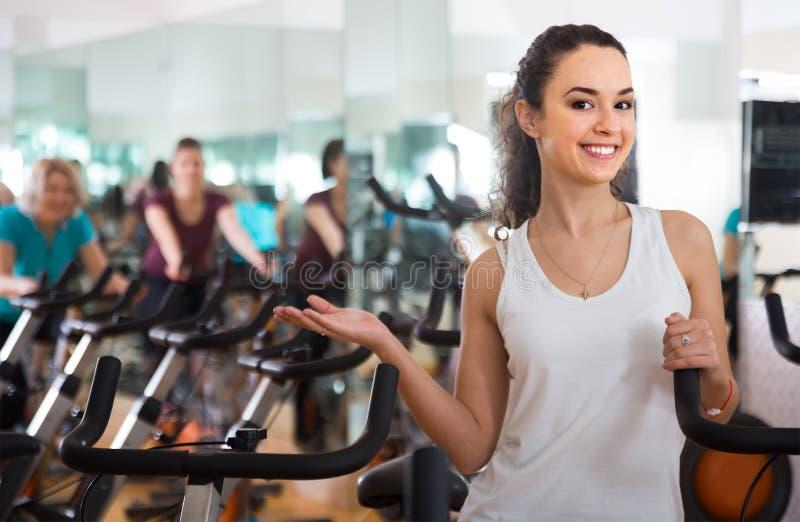 实践在锻炼脚踏车的年轻微笑的女孩 库存照片