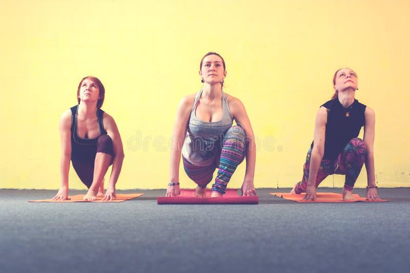 实践在类的三个女性成人瑜伽 免版税库存照片