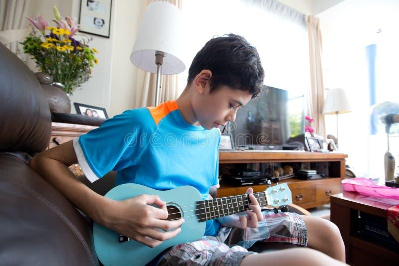 实践在他的蓝色ukelele的年轻泛亚男孩在一个家庭环境里 免版税库存照片