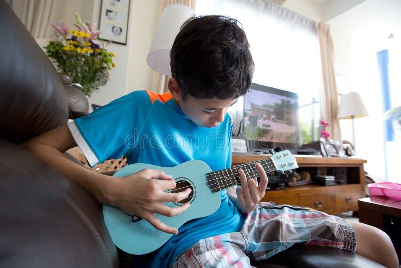 实践在他的蓝色ukelele的年轻泛亚男孩在一个家庭环境里 免版税库存图片