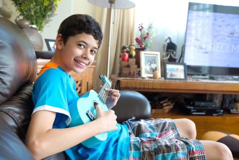 实践在他的蓝色ukelele的年轻泛亚男孩在一个家庭环境里 库存图片