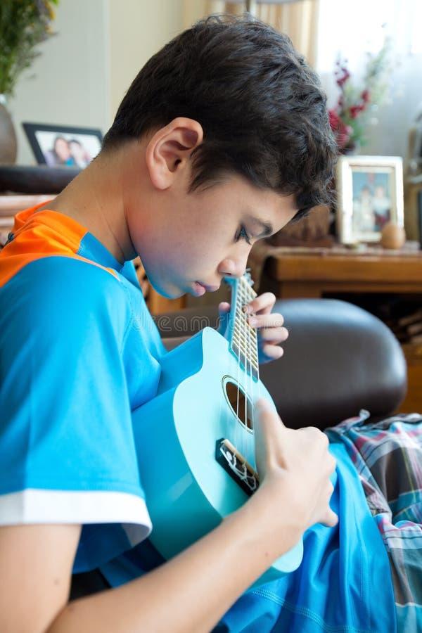 实践在他的蓝色ukelele的年轻泛亚男孩在一个家庭环境里 免版税图库摄影
