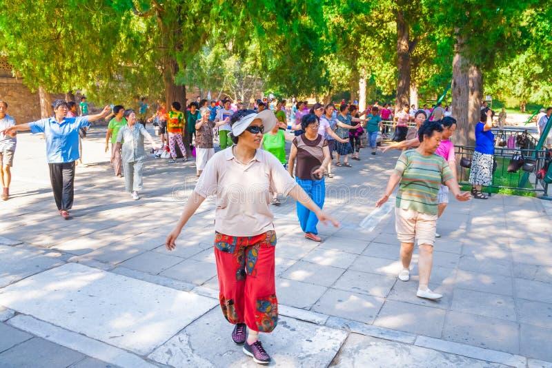 实践太极拳的小组更老的亚裔妇女在一个庭院里在北京,中国 免版税库存图片