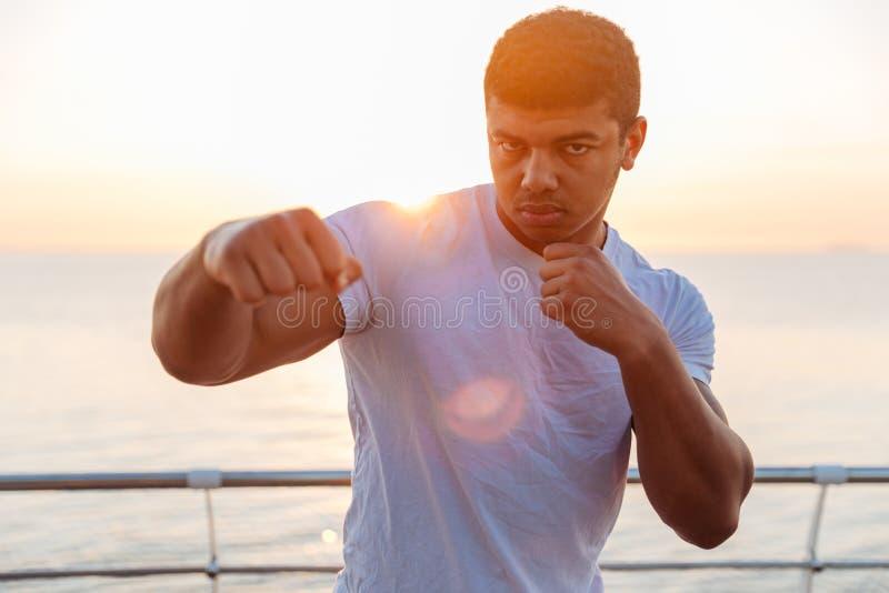 实践武术的英俊的非洲人拳击手早晨 库存图片